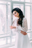 Luxurious brunette in a white vintage dress. Luxurious brunette in a white dress standing in a white clean room with light leaning against the window , a stock image