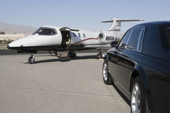 Luxurious Car And Airplane. Luxurious black car with private airplane at airfield royalty free stock photo