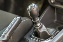 Luxurious car black leather interior. Close-up detail of handbrake manual brake and gearshift stick on blurred dashboard. Background. Transportation, design royalty free stock photo