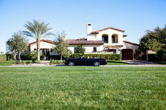 Luxurious car parked outside house in front yard Royalty Free Stock Images