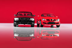 Luxurious cars. Two expensive and luxurious cars with red background Royalty Free Stock Images