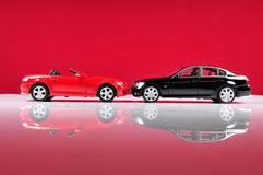 Luxurious cars. Two expensive and luxurious cars with red background Stock Photography
