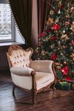 Luxurious chair in the interior. New Year celebration. Christmas tree decorated with toys and a garland. Luxurious chair in the interior. New Year celebration Royalty Free Stock Images