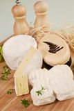 Luxurious cheese variation. Luxurious cheese variation arranged on wooden board with fresh herbs stock image