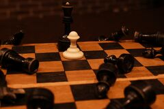 Luxurious chess king opposing shabby pawns in concept of social inequality.