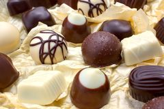 Luxurious chocolates. Decorative black and white chocolates arranged on yellow paper background Stock Photography