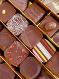 Luxurious chocolates. A photograph showing a few rows of expensive luxury chocolates in a beautiful golden box. Assorted chocs in different flavors, with royalty free stock photography
