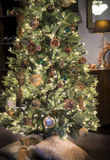 Luxurious christmas tree. Christmas tree richly decorated with golden, silver and green balls, stars with tassels and lights on brown background with lamp and Stock Images