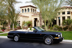 Luxurious convertible car parked in front of a mansion house Stock Photography