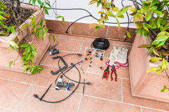 Luxurious copper drip irrigation system, with copper pipes. Micro irrigation system for pot plants on a terrace of a house   Royalty Free Stock Photography