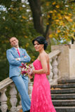 Luxurious couple, brunette stands sideways in a bright pink tigh. Beautiful women in pink sophisticated dress with bare shoulders and bouquet at arms.In royalty free stock photo