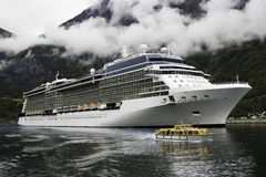 A luxurious cruise ship anchored near a Norwegian fjord village Flam during the summer months. A  a low angle image of a luxurious cruise ship anchored near a Stock Image