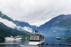 A luxurious cruise ship anchored near a Norwegian fjord village of Flam during the summer months. A landscape image of three luxurious cruise ships anchored near Stock Photography