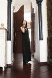 Luxurious dark-haired woman in a black dress and a massive gold jewelry stands in the doorway. Royalty Free Stock Photography