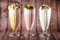 Nice drinks with a lot of ice cream in combination with mint, green apple, cocoa, vanilla. Luxurious decoration of different milkshakes: chocolate chips, cookie Stock Photos