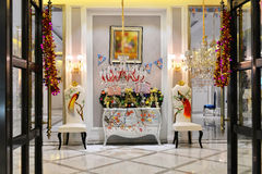 Luxurious decoration of the hall for holiday. Modern home interior at Christmas time, luxury crystal lighting, marble floor, leather chair, silver table Stock Image