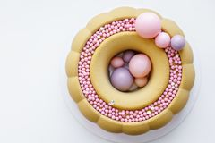 Luxurious round dessert with pink chocolate spheres. Yellow mousse birthday cake with multicoloured sweet sugar balls