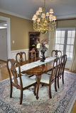 Luxurious dining room. Luxurious wooden dining room table and chairs in a modern home Royalty Free Stock Photography