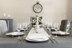A luxurious dining room of a house with glasses and plates. In the dining room of a house an elegant table in gray and white tones, a vintage clock hangs on the royalty free stock photos