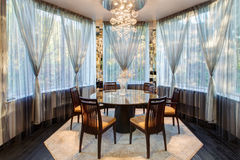 Luxurious dining room. With panoramic windows roudn table and chairs Royalty Free Stock Image