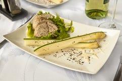 Luxurious dinner - pork sirloin with asparagus and wine. Tasty dinner - pork sirloin with asparagus and white wine Stock Photos
