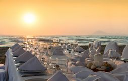 Luxurious dinner table setup on the beach. During sunset stock photos
