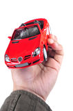 Luxurious dream. Male hand holding luxurious car toy in han over white background Stock Photo