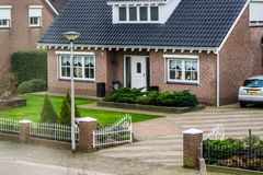 Luxurious dutch bungalow from street view, with beautiful garden and a gate, modern dutch architecture, home in a small village of. A luxurious dutch bungalow royalty free stock image