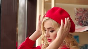 Portrait of a young girl in a red dress and hat near the window. Art. A luxurious elegant girl with bright make-up in a red dress and a red hat stands near the stock footage
