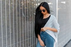 Luxurious elegant pretty young hipster woman in trendy jeans in a black t-shirt in a summer cape in sunglasses with long hair. Rests standing near a vintage royalty free stock photography