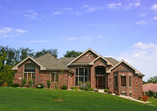 Luxurious executive home. Luxurious brick executive home with blue sky and green grass Royalty Free Stock Photography