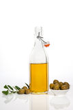 Luxurious extra virgin olive oil background. Olive oil in glass bottle, olives in bowl and fresh olive branch and leaves on white background. Culinary cooking Stock Photo