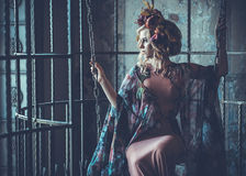 Luxurious  fashion stylish girl  in cage. Flower dress and a wr Stock Photo