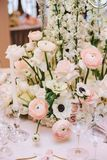 Luxurious flower arrangement of buttercups, white roses on a banquet table, along with candlesticks and glasses for wine royalty free stock photo