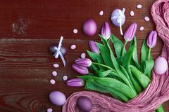 Luxurious fresh fashionable purple tulips on a wooden background next to Easter eggs.  Stock Photos