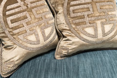 Luxurious Gold Cushions on Expensive Blue Sofa Royalty Free Stock Photography
