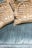 Luxurious Gold Cushions on Expensive Blue Sofa Royalty Free Stock Images