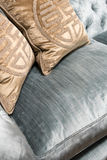 Luxurious Gold Cushions on Expensive Blue Sofa Royalty Free Stock Image
