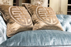Luxurious Gold Cushions on Expensive Blue Sofa Stock Images