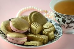 Luxurious gold French macarons and chocolates on a porcelain plate. Gold and pink French macarons, chocolates with a cup of tea, pearls Royalty Free Stock Photography