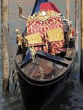 Luxurious gondola in Venice on a canal. Gondola in Venice in Italy with cozy seats, ornaments, statues and romance royalty free stock image