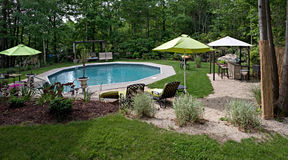 Luxurious In Ground Pool. A wide angle panoramic view of a luxurious in ground pool and patio. This partly wooded backyard offers the same level of luxury found royalty free stock images