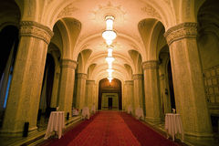 Luxurious hallway. A picture of a luxurious palace hallway, with a red carpet running down the middle and small cocktail tables along the sides Stock Images