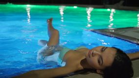 Luxurious holiday of sexy female into colored Swimming-pool in night at summer vacation. Luxurious holiday of sexy female into colored Swimming-pool in night at stock footage