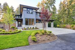 Luxurious home design with modern curb appeal in Bellevue. Luxurious new home with curb appeal. Trendy grey two-story mixed siding exterior in Bellevue with a Royalty Free Stock Images
