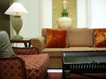 Luxurious hotel room. Lush room interior with sofas, table and vase with lamp Royalty Free Stock Photo