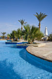 Luxurious hotel swimming pool. Surrounded by palm trees and bushes, Sharm el Sheikh resort, Egypt stock images