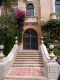 Luxurious house entrance. Brick walls with lots of vegetation, wrought iron gate,  marble stairs Stock Image