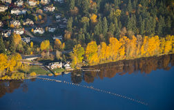 Luxurious House By the Lakeside on Calm Day. Aerial view of yellow trees reflecting off of calm lake water next to a wealthy residence Royalty Free Stock Image