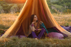Luxurious Indian girl is sitting in a tent outdoors, at sunset. Royalty Free Stock Photos